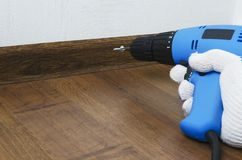 Repair work indoor.Man screwing a bolt.Fixing of skirtings boards by using special instrument. Man in gloves preparing a screwdriver for repair works at home stock photography