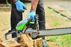A man in gloves starts a chainsaw. To spray a log stock photos
