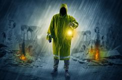 Man with a glowing lantern at a catastrophe scene. Destroyed place after a catastrophe with man in raincoat and lantern conceptn royalty free stock photo