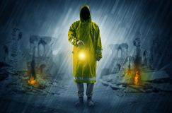 Man with a glowing lantern at a catastrophe scene. Destroyed place after a catastrophe with man in raincoat and lantern conceptn Stock Photos