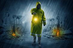 Man with a glowing lantern at a catastrophe scene. Destroyed place after a catastrophe with man in raincoat and lantern conceptn Stock Photography