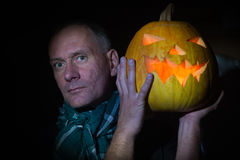 Man with glowing pumpkin peering into darkness Stock Photography