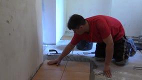 Man glue ceramic tile on kitchen floor at home stock video
