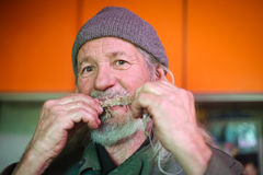 Man gnawing bone. A front view of an old man gnawing on a pork bone and looking at camera Stock Images