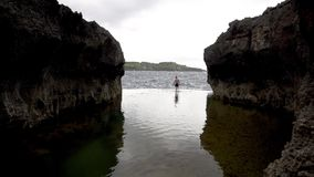 Man go to ocean at Angel's Billabong beach on island Nusa Penida, Indonesia. Man go to ocean at Angels Billabong beach, the natural pool on the island of Nusa stock video footage