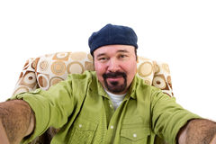 Man with goatee in armchair taking selfie Stock Image