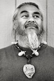 Man with Goatee & Necklace. Black and white portrait of a man with goatee and necklace made of abalone, seeds, and cocoons Stock Image