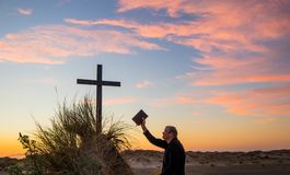 Man of Gods Word. Man holding up The Bible to a cross on a sand hill, with a wonderful sunset sky royalty free stock photos