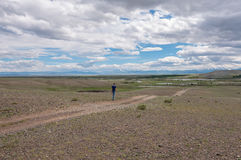 man goes along dirt road steppe sky Royalty Free Stock Photography