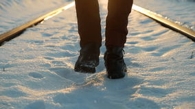 Man goes along the rail at sunset in winter stock footage