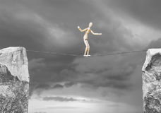 Man goes along a rope over the precipice Stock Photo