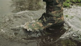 A man goes in army boots. The hunter walks in camouflage boots. A man in army boots. The soldier overcomes obstacles stock footage