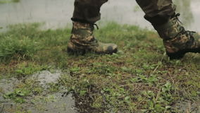 A man goes in army boots. A man in army boots. The hunter walks in khaki boots. The soldier overcomes obstacles stock footage