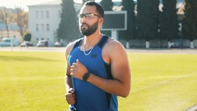 Man goes jogging in stadium. Intelligent young man going jogging in big stadium, wearing blue vest and gray tracksuit bottoms on warm sunny weekend stock video