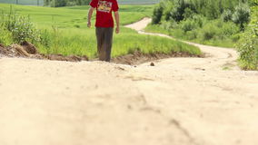 Man goes on a long road near the field stock footage