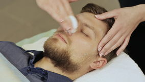 A man goes through the procedure of cleaning his face in the spa center. Hyaluronic mask. A man goes through the procedure of cleaning his face in the spa stock video
