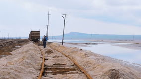 Man goes by rail. Tourist walking on cross ties to old wagons. Old rusty railroad through salt lake. Saline salt lake Baskunchak R. Man goes by rail. Tourist stock video footage