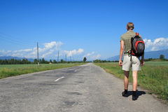 Man goes on road. Man in the summer, with a backpack on a back, goes on road Royalty Free Stock Photos
