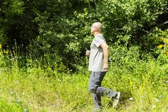 A man goes in for sports. Overweight man running in nature stock images
