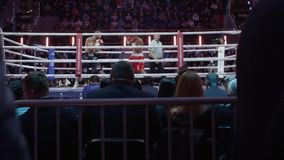 Man goes to a Boxing ring during a fight. The first person. Lot of people in large hall on fighting event. stock footage