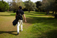 Man goes to the cafe after winning the golf tournament. Rear view of professional male golfer walking to the next hole in golf course, good golf game at sunny stock photos