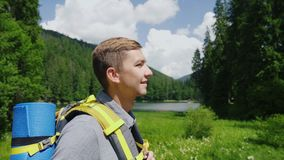 An attractive tourist man goes to a picturesque place in the background of meadows, mountains and sky. Tourism and. Man goes to a picturesque place in the stock footage