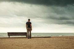 Man goes to the sea near old wooden empty bench Stock Photo