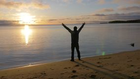 A man goes to the shore of the lake. He raises his hands up and salutes the sun. A great start to a new day. 4K stock footage