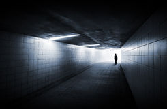 Man goes on underground passage. With neon lights and glowing end Royalty Free Stock Photography