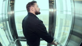 Man goes up into a glass elevator. Man into a glass elevator going up and out stock video footage