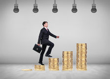 Man goes up by stairs from coins. Royalty Free Stock Photo