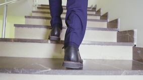 Man goes up stairs slow motion low angle shot closeup. Manager in stylish shoes goes up stairs in modern business center slow motion low angle shot closeup stock video footage