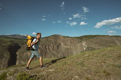 Man goes uphill with a backpack on his back stock photography