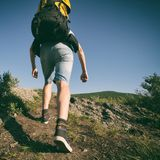 Man goes uphill with a backpack on his back royalty free stock image