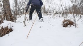 Man goes on wild forest in the snow climb the mountain winter landscape Stock Photography