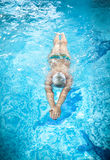 Man in goggles swimming under water at swimming pool. Young man in goggles swimming under water at swimming pool Stock Photo