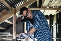 Man in goggles and wipes his forehead from sweat when handling wooden boards planer, heavy manual labor, handyman. Diy stock photos