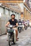 Man going across Long Bien steel bridge in Hanoi. On a moped Royalty Free Stock Photo