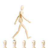 Man going ahead on the heads of other people. Concept of arrogance and hubris. Abstract image with a wooden puppet Stock Photo