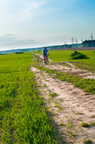 Man going on the green meadow with bike Royalty Free Stock Photos