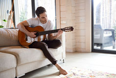 Man going in for hobbies. Pretty young man playing guitar while sittinh on sofa in light living room Royalty Free Stock Photo