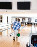 Man Going For The Last Pin in Bowling Alley. Rear view of young man going for the last pin in bowling alley Royalty Free Stock Photography