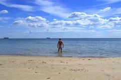 Man going into the sea view stock photos