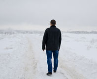 The man going on a snow field. In winter evening Stock Photos