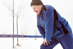 Man going in for sport in the winter on snow. Man warming up before running in the winter on snow Stock Photo
