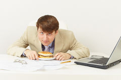Man is going to have dinner hamburger at office Stock Photo
