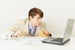 Man is going to have dinner sandwich at office Royalty Free Stock Image