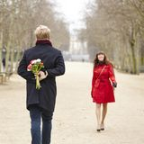 Man is going to offer flowers to his girlfriend Stock Photos