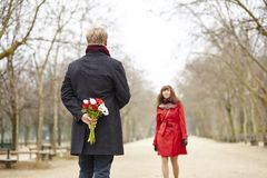 Man is going to offer flowers to his girlfriend. Happy couple having a date, men is going to offer flowers to his girlfriend royalty free stock photo