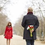 Man is going to offer flowers to his girlfriend Stock Photo